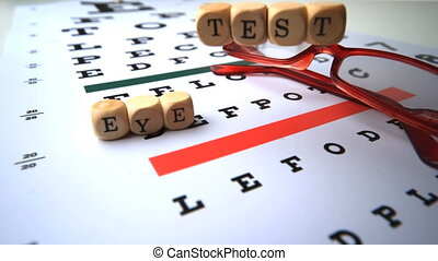 Eye test dice falling on eye test with reading glasses in...