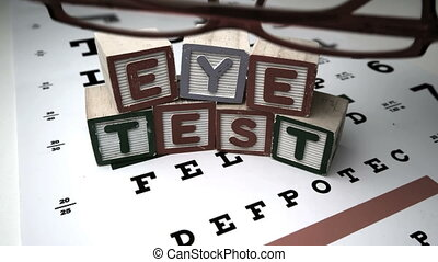 Red glasses falling onto eye test next to blocks spelling...