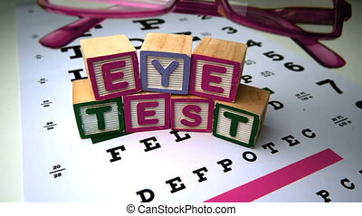 Pink glasses falling next to blocks spelling out eye test in...