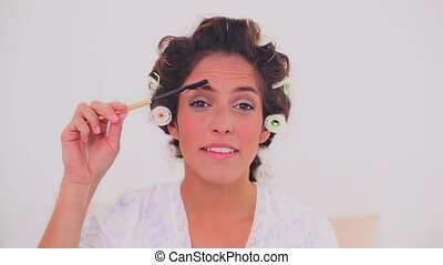 Smiling woman in hair curlers - Smiling brunette woman in...