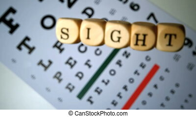 Dice spelling out sight falling on eye test in slow motion