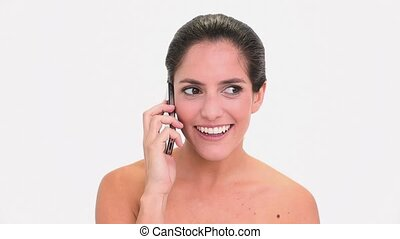 Amused brunette woman making a phone call on white...