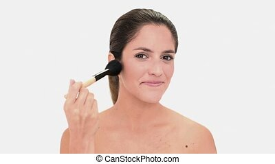 Concentrated brunette woman applying blush on white...