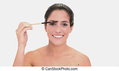 Concentrated brunette woman brushing eyebrows - Concentrated...