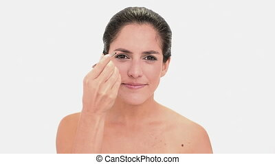 Attractive brunette woman plucking her eyebrow on white...
