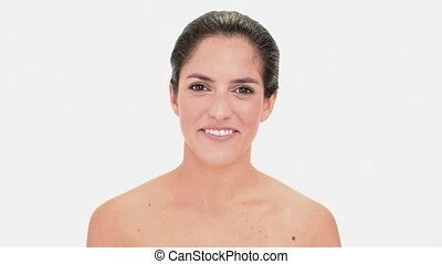 Pretty brunette woman applying gloss on white background