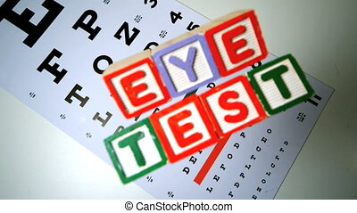 Colorful blocks spelling out eye test falling onto eye test...