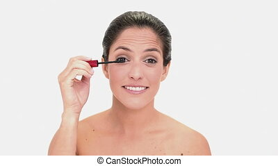 Thoughtful brunette woman applying mascara on white...