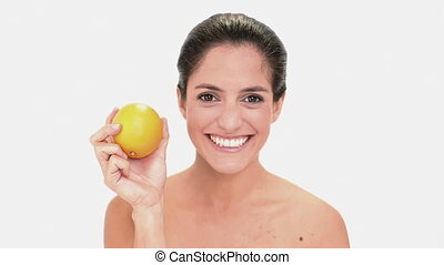 Calm brunette woman holding and smelling an orange