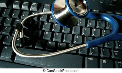 Blue stethoscope falling onto keyboard - Blue stethoscope...
