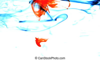 Blue and red ink swirling in water on white background in...