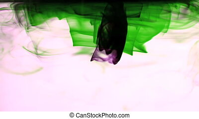 Pink and green ink swirling in water on white background in...