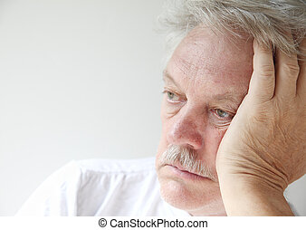 older man looking off into space - senior man gazes into the...