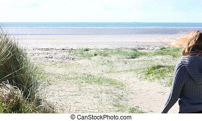 Woman walking on a beach in windy weather - Woman walking on...