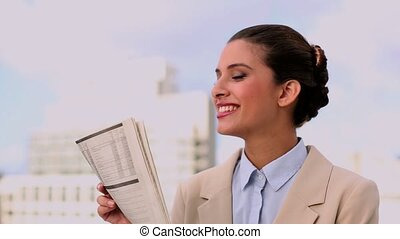 Delighted beautiful businesswoman reading newspaper outdoors