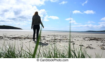Woman relaxing and walking towards the sea on the beach