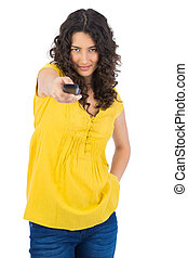 Curly haired pretty woman holding remote - Curly haired...