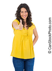 Smiling casual young woman posing thumbs up on white...