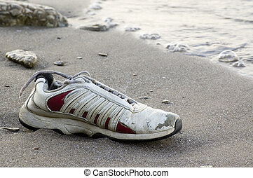 Shoe on Beach - Old running shoe sitting on a beach with...