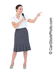 Attractive presenter holding microphone pointing while...