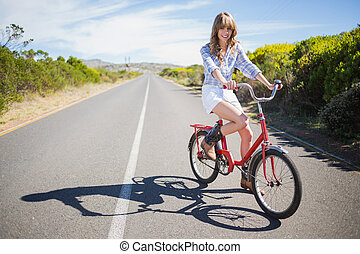 Smiling young model posing while riding bike down a deserted...