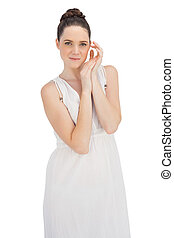 Natural young model in white dress posing on white...