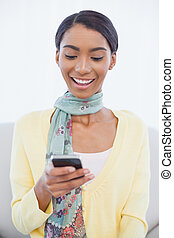 Young pretty woman sitting on sofa text messaging - Young...