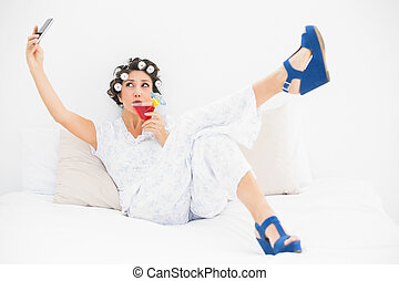 Brunette in hair rollers and wedge shoes drinking a cocktail...