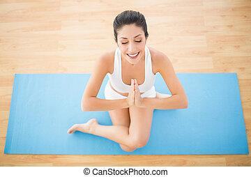 Fit woman meditating in cow face pose at home on wooden...