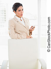 Frowning businesswoman standing behind her chair holding her...