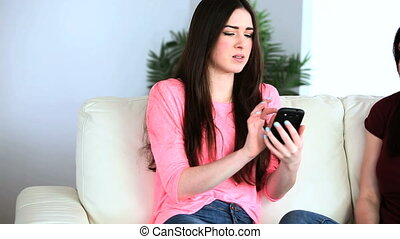 Brunette woman picking up her smartphone and listening to...