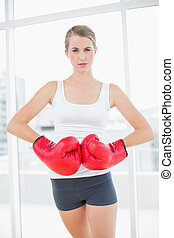 Competitive woman with red boxing gloves posing in bright...