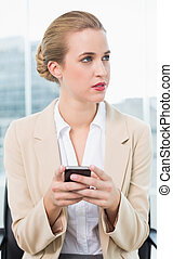 Pensive attractive businesswoman text messaging - Pensive...
