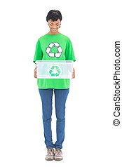 Content black haired ecologist holding a recycling box on...