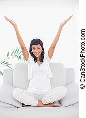 Pleased black haired woman in white clothes raising her arms...