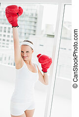Cheering pretty sportswoman raising her boxing glove in a...