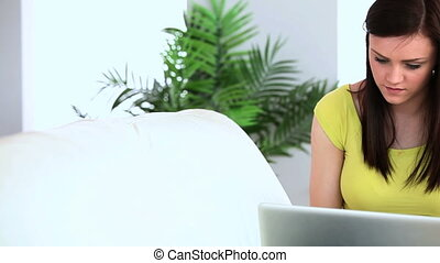 Brunette woman typing on her laptop