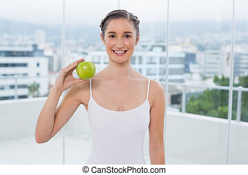 Cheerful sporty brunette holding green apple
