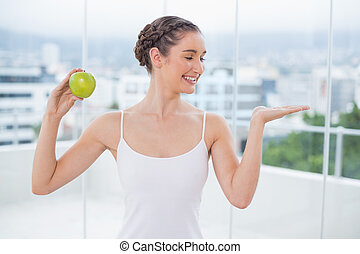 Happy sporty brunette holding green apple