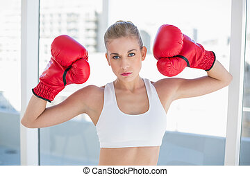 Dynamic young blonde model wearing boxing gloves - Dynamic...