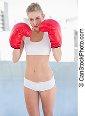 Serious young blonde model exercising with boxing gloves -...