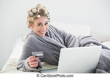 Joyful relaxed blonde woman in hair curlers buying online...