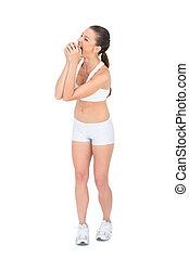 Fit woman in sportswear munching apple on white background