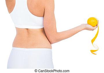 Rear view of fit woman in sportswear holding peeled orange