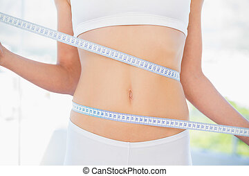 Mid section of woman measuring her waist in bright fitness...