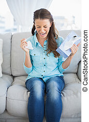 Troubled woman crying sitting on sofa in bright living room