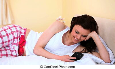 Cheerful woman texting on her bed and looking at camera