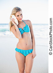 Happy gorgeous blonde in bikini holding shell by her ear on...