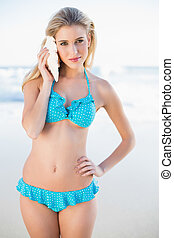 Relaxed gorgeous blonde in bikini holding shell by her ear...