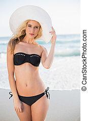 Sexy blonde in elegant bikini wearing straw hat posing on a...